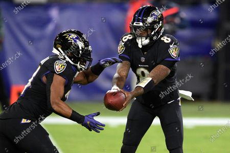 Baltimore Ravens quarterback Lamar Jackson, right, hands off to running back Mark Ingram during the first half of an NFL football game against the Dallas Cowboys, in Baltimore