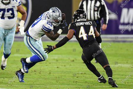 Dallas Cowboys running back Ezekiel Elliott (21) runs the ball against Baltimore Ravens cornerback Marlon Humphrey (44) during the second half of an NFL football game, in Baltimore