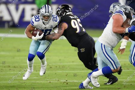 Dallas Cowboys running back Tony Pollard (20) runs with the ball against Baltimore Ravens defensive end Derek Wolfe (95) during the first half of an NFL football game, in Baltimore