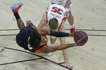 Idaho State guard Robert Ford III, foreground, tries to get a shot off against Utah Utes center Branden Carlson (35)during the first half of an NCAA college basketball game, in Salt Lake City