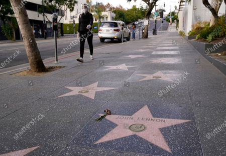 Masked pedestrian walks by John Lennon's star on the Hollywood Walk of Fame, in front of the Capitol Records building in Los Angeles. Tuesday marked the 40th anniversary of Lennon's death, but Los Angeles' shutdown order due to COVID-19 concerns precluded the annual celebration of his legacy at the star