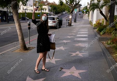 Lifelong Beatles fan Mikayla Beyer of Burbank, Calif. takes a selfie at John Lennon's star on the Hollywood Walk of Fame, in front of the Capitol Records building in Los Angeles. Tuesday marked the 40th anniversary of Lennon's death, but Los Angeles' shutdown order due to COVID-19 concerns precluded the annual celebration of his legacy at the star