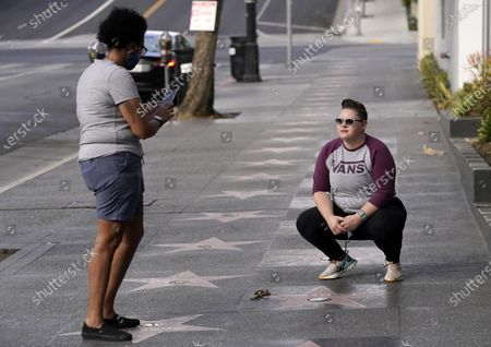 Danielle Tucker, left, takes a photo of her wife Maelea at John Lennon's star on the Hollywood Walk of Fame, in front of the Capitol Records building in Los Angeles. Tuesday marked the 40th anniversary of Lennon's death, but Los Angeles' shutdown order due to COVID-19 concerns precluded the annual celebration of his legacy at the star