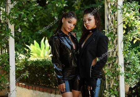 """In this photo, Halle Bailey, left, and her sister Chloe Bailey, of the R&B duo Chloe X Halle, pose for a portrait in their backyard in Los Angeles to promote their latest release, """"Ungodly Hour."""" The duo's song """"Do It"""" was named one of the top 10 of the year by the Associated Press"""