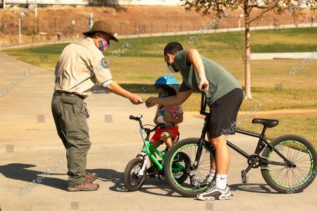 California State Park Ranger for Community Engagement Ban Luu, left, gives stickers to Dennis Ignacio and his son Cameron Ignacio, 3, as they ride through Los Angeles State Historic Park on Thursday November 19, 2020 where a company funded by former Dodgers owner Frank McCourt has proposed a $125 million gondola lift that would fly customers over Los Angeles State Historic Park from Union Station to Dodger Stadium and activists are weighing in. Parents with children and local residents savored the grand opening of the new park in 2017 sandwiched between Chinatown and the L.A. River. Los Angeles State Historic Park, about a 10-minute walk from City Hall, has blossomed into a popular 32-acre urban oasis. Los Angeles State Historic Park on Thursday, Nov. 19, 2020 in Los Angeles, CA. (Al Seib / Los Angeles Times