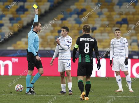 Referee from Sweden Andreas Ekberg shows a yellow card to Carlos de Pena  of Dynamo  during the UEFA Champions League group G football match at the Olimpiyskiy stadium