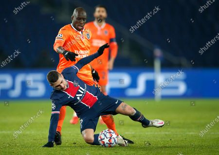 PSG's Marco Verratti, left, and Basaksehir's Demba Ba challenge for the ball during the Champions League group H soccer match between Paris Saint Germain and Istanbul Basaksehir at the Parc des Princes stadium in Paris, France