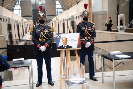 Republican guards stand next to a picture of late former French President Valery Giscard d'Estaing as people arrive to sign the guest book at the Musee d'Orsay in Paris on the national day of mourning for the former president. Valery Giscard d'Estaing died from Covid-19 aged 94, surrounded by his family on December 2 at the family estate. Giscard governed for a single seven-year term from 1974 to 1981.