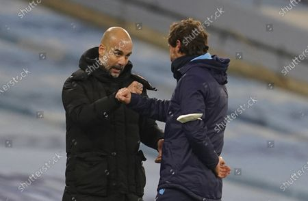 Manchester City's head coach Pep Guardiola, left, cheers Marseille's head coach Andre Villas-Boas end of the Champions League, Group C, soccer match between Manchester City and Marseille at the Etihad stadium in Manchester in London . Manchester City won 3-0