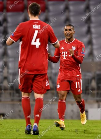 Bayern Munich's Niklas Suele (L) celebrates with teammate Douglas Costa (R) after scoring the 1-0 lead during the UEFA Champions League group A soccer match between Bayern Munich and Lokomotiv Moscow in Munich, Germany, 09 December 2020.