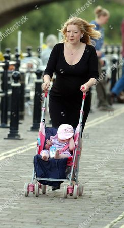 A Pregnant Rachel Lewis With The Army Officer's Love Child Walking In Her Home Town. One Of The Militay's Most Senior Communications Chiefs Has Been Suspended After Fathering A Love Child During A Torrid 15-month Affair. Colone Fred Chedham 43 Is Being Investigated Over Claims He Arranged Trysts At Top Hotels With Single Mother Rachel Lewis While On Official Army Business. The Army's A60 000-a-year Director Of Corporate Communicatins Is Also Accused Of Using His Military Postion To 'frighten Off' A Fellow Officer Who Had Become Friendly With His 27-year-old Mistress A Liberal Party Councillor In Bewdley Worcestershire. The Couple Split Up In December Last Year-after Mrs Lewis Fell Pregnant With His Second Child. She Is Due To Give Birth To A Daughter On August 27 The First Birthday Of Their Daughter Alice. Mrs Lewis Who Has Three Other Children From Two Previous Relationships Has Refused To Comment About The Case. But In A Statmtn Given To The Royal Military Police-leaked To The Daily Mail-she Reveals How The Colonel Whom She Called Freddy Was 'sex Obsessd' And Gave Her His Uniforms To Wear During Lovemaking. The Colonel Who Has Four Children With His Wife Alison Also Asked The Strawberry Blonde Councillor To Go Shopping Without Any Knickers On During A Business Weekend Away In Edinburgh. She Claimed That He Told Her The Though Would 'excite' Him While He Was At A Meeting. Mrs Lewis Said That Col Chedham 'implied' That The Hotels They Stayed In Would Be Paid For By The Army. Yesterday There Was No Sign Of The Colonel At His A300 000 Cottage In The Village Of Stoke St Gregory Somerset. His Wife Refused To Comment On The Allegations. Pix Bould Story Dolan.
