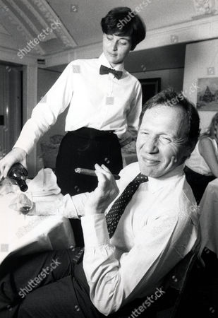 Anthony Haden-guest Enjoys A Cigar As A Waitress Pours Him A Glass Of Wine. Journalist Anthony Haden-guest Was Born In Paris On 2 February 1937. The Son Of Peter Haden-guest And Grandson Of Leslie Haden Haden-guest A Labour Mp.