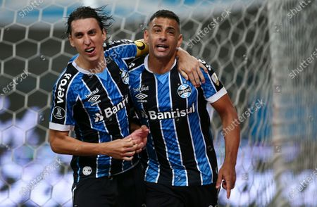 Diego de Souza of Brazil's Gremio, right, celebrates with teammate Pedro Geromel after scoring his side's first goal from the penalty spot during a Copa Libertadores quarterfinal first leg soccer match against Brazil's Santos at the Gremio Arena in Porto Alegre, Brazil