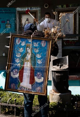 Stock Picture of Alejandro Gonzalez is sprinkled with holy water by a priest as he carries an image of the Virgin of Guadalupe on his back, outside the Basilica of the Virgin of Guadalupe in Mexico City, . Gonzalez departed from his home in San Gregorio Atzompa, Puebla state to make the pilgrimage to the Basilica on Dec. 6, and made it to the temple a day before it closed to the public due to the COVID-19 pandemic