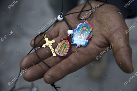 Stock Image of Alejandro Gonzalez shows his medals of the Virgin of Guadalupe during a pilgrimage along with his family and friends to the Basilica of the Virgin of Guadalupe in Mexico City, . The group departed their home in San Gregorio Atzompa, Puebla state, to make the pilgrimage to the Basilica on Dec. 6, and made it to the temple a day before it closed to the public due to the COVID-19 pandemic