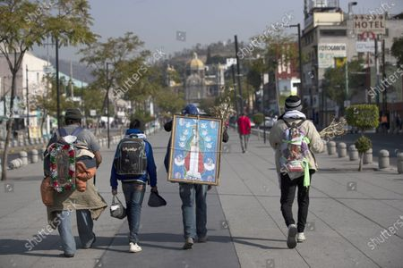 Alejandro Gonzalez carries an image of the Virgin of Guadalupe on his back as he makes a pilgrimage along with his family and friends to the Basilica of the Virgin of Guadalupe in Mexico City, . The group departed their home in San Gregorio Atzompa, Puebla state, to make the pilgrimage to the Basilica on Dec. 6, and made it to the temple a day before it closed to the public due to the COVID-19 pandemic