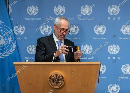 Spokesman for Secretary-General Stephane Dujarric De La Riviere takes photo with cell phone during UN Secretary-General Antonio Guterres hybrid press stakeout with Chairperson of the AU Mr. Moussa Faki Mahamat at UN Headquarters. Chairperson of the African Union Moussa Faki Mahamat participating via teleconference from his office because of pandemic. Press briefings conducted at UN Headquarters are held in a hybrid manner: handful of journalists attend in person keeping social distance and others via video link.