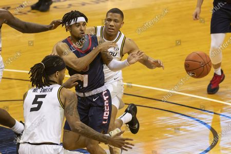 Liberty's Chris Parker, center, passes the ball away from Missouri's Mitchell Smith, left, and Javon Pickett during the first half of an NCAA college basketball game, in Columbia, Mo