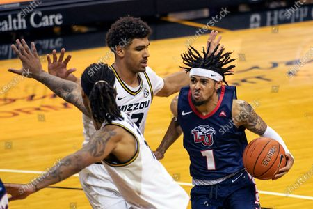 Liberty's Chris Parker, right, tries to drive past Missouri's Mark Smith, center, and Mitchell Smith during the first half of an NCAA college basketball game, in Columbia, Mo. Missouri won 69-60