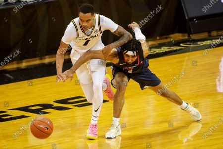 Missouri's Xavier Pinson, left, battles Liberty's Chris Parker, right, for a loose ball during the second half of an NCAA college basketball game, in Columbia, Mo. Missouri won 69-60