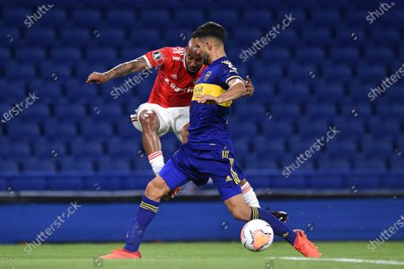 Eduardo Salvio of Argentina's Boca Juniors, right, and Patrick of Brazil's Internacional battle for the ball during a Copa Libertadores soccer match in Buenos Aires, Argentina