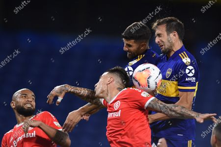 Patrick, left, and Victor Cuesta, center, of Brazil's Internacional, fight for the ball with Eduardo Salvio, second right, and Carlos Izquierdoz of Argentina's Boca Juniors during a Copa Libertadores soccer match in Buenos Aires, Argentina