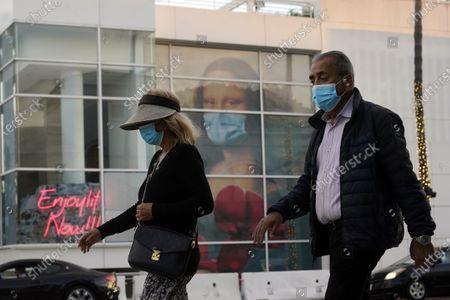 Masked pedestrians walk past of a COVID 19-themed mural depicting Leonardo da Vinci's Mona Lisa, in Beverly Hills, Calif