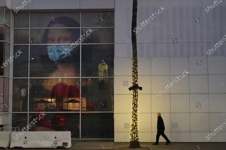 Masked pedestrian walks past of a COVID 19-themed mural depicting Leonardo da Vinci's Mona Lisa, in Beverly Hills, Calif