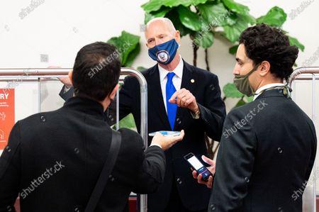 U.S. Senator Rick Scott wearing a face mask (R-FL) speaks with reporters  at the Senate Subway.