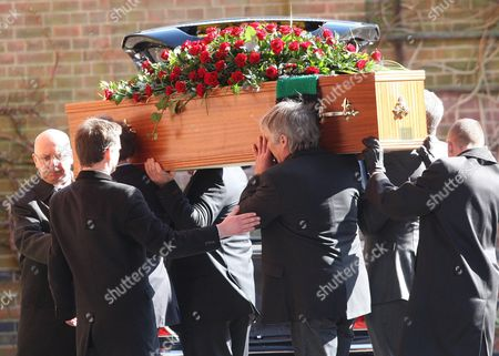 The coffin with a Plymouth Argyle FC scarf on the back