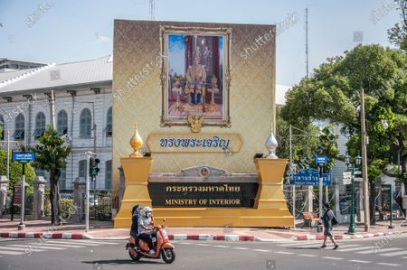 A motorcyclist rides past a portrait of King Maha Vajiralongkorn in front of the Ministry of Interior.