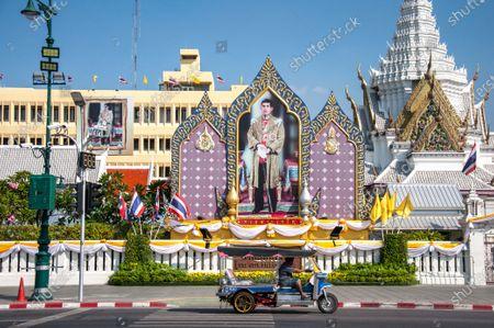 A Tuk Tuk (An auto rickshaw) rides past a portrait of King Maha Vajiralongkorn (King Rama X).