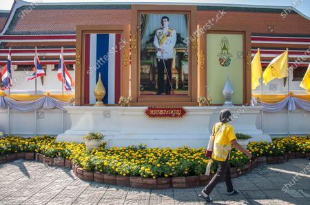 A woman walks past a portrait of King Maha Vajiralongkorn (King Rama X).
