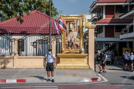 A student with crutches stands in front of a portrait of King Maha Vajiralongkorn (King Rama X) outside the school.