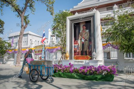 A street vendor push a cart past  a portrait of King Maha Vajiralongkorn (King Rama X).
