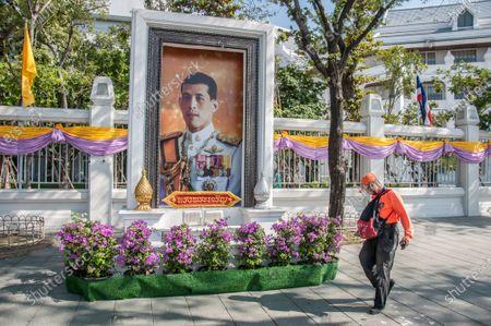 A man walks past a portrait of King Maha Vajiralongkorn (King Rama X).