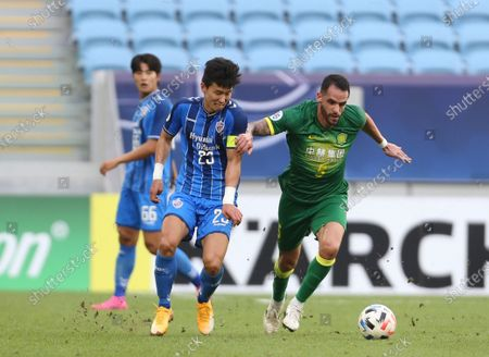 Ulsan Hyundai's Kim Tae-Hwan, left, and Beijing's Renato Augusto fight for the ball during a quarter final AFC Champions League match in Al Wakrah, Qatar