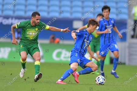 Lee Chung-Yong (C) of Ulsan in action against Renato Augusto (L) of Beijing during the AFC Champions League Quarter Finals match between Ulsan Hyundai FC and Beijing FC at the Al-Janoub Stadium in Al-Wakrah, Qatar, 10 December 2020.
