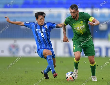Renato Augusto (R) of Beijing in action against Sin Jin-Ho (L) of Ulsan reacts during the AFC Champions League Quarter Finals match between Ulsan Hyundai FC and Beijing FC at the Al-Janoub Stadium in Al-Wakrah, Qatar, 10 December 2020.