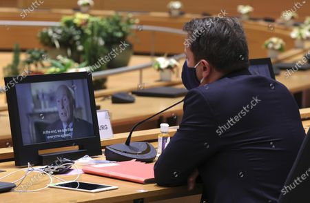 Luxembourg's Prime Minister Xavier Bettel, watches a screen with a short film to remember late French President Valery Giscard d'Estaing during a round table meeting at an EU summit in Brussels, . European Union leaders meet for a year-end summit that will address anything from climate, sanctions against Turkey to budget and virus recovery plans. Brexit will be discussed on the sidelines. Screen dialogue reads 'In the end, we saw that everyone agreed