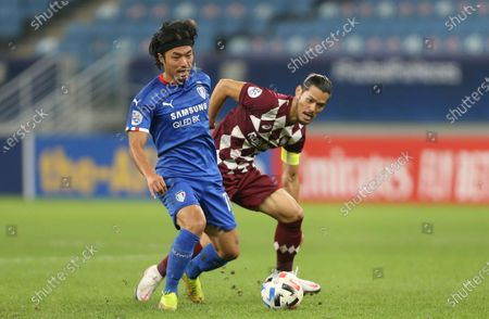 Suwon Samsung Bluewings' Ko Seung-Beom, left, fights for the ball with Vissel Kobe's Hotaru Yamaguchi during the Champions League, quarter final, soccer match between Vissel Kobe and Suwon Samsung Bluewings in Doha, Qatar