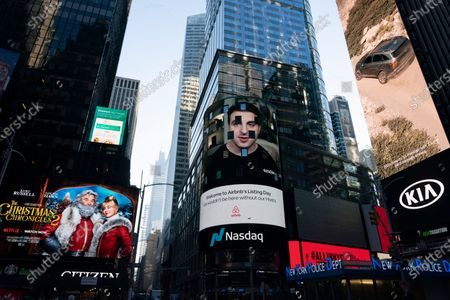 Brian Chesky, CEO of Airbnb, is shown on an electronic screen, center, at the Nasdaq MarketSite, in New York. The San Francisco-based online vacation rental company holds its IPO Thursday