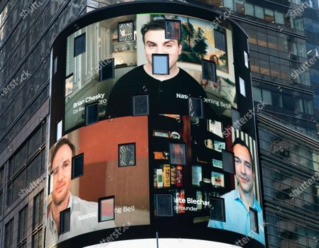 The electronic screen at the Nasdaq MarketPlace displays the Airbnb co-founders Brian Chesky, top, Joe Gebbia, left, and Nathan Blecharczyk, right, in New York. The San Francisco-based online vacation rental company holds its IPO Thursday