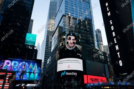 Stock Photo of Brian Chesky, CEO of Airbnb, is shown on an electronic screen, center, at the Nasdaq MarketSite, in New York. The San Francisco-based online vacation rental company holds its IPO Thursday