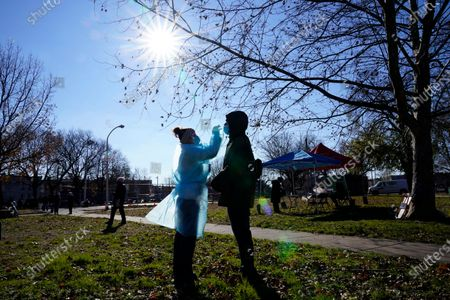 Registered nurse Laura Moore, left, swabs Andry Laurens during testing for COVID-19 organized by Philadelphia FIGHT Community Health Centers at Mifflin Square Park, in south Philadelphia