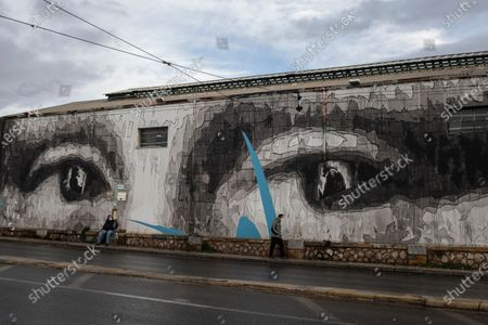 Two men wearing face masks to prevent the spread of the coronavirus walk past a giant mural by Greek street artist iNO depicting the eyes of Leonardo da Vinci's Mona Lisa, in Athens, . The government said it will maintain core lockdown measures through the Christmas holidays, acknowledging that month long restrictions have not reduced COVID-19 cases to the extent it had hoped for
