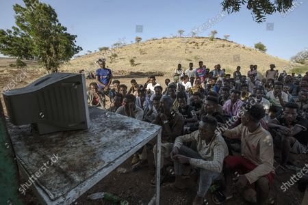Men who fled the conflict in Ethiopia's Tigray region watch news on a television at the Umm Rakouba refugee camp in Qadarif, eastern Sudan, . Ethiopian and the regional Tigray governments consider each other illegitimate after a power struggle since Prime Minister Abiy Ahmed took office two and a half years ago