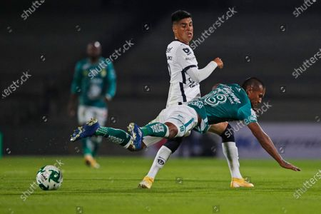 Pumas' Leonel Lopez, back, and Leon's Pedro Aquino fight for the ball during their Mexican soccer league final first leg soccer match at University Olympic Stadium in Mexico City