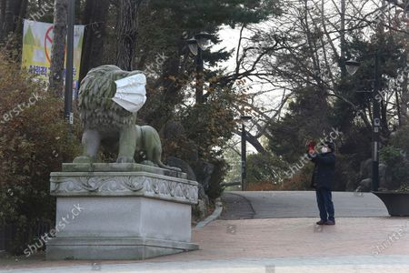 Woman wearing a face mask as a precaution against the coronavirus takes a picture of a lion statue with a face mask at a park in Seoul, South Korea, . South Korea is expanding the use of rapid tests and deploying hundreds of police officers and soldiers to help with contact tracing as it deals with its worst surge of coronavirus cases since the early days of the pandemic