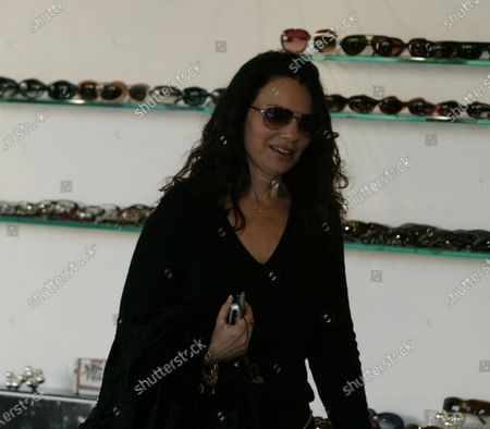 Fran Drescher who starred on the sitcom the nanny walks arm in arm along Robertson Boulevard in Beverly Hills, Ca with her former husband Peter Marc Jacobson who she seems to have reunited with as they were all smiles as they left a sunglasses store and walked along the popular street